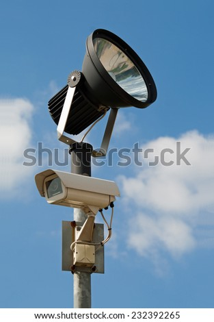Surveillance camera with floodlight, blue cloudy sky - stock photo