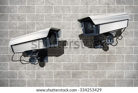 Surveillance Cameras watching each other on brick wal - stock photo