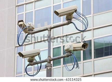 Surveillance security video camera in urban setting - stock photo