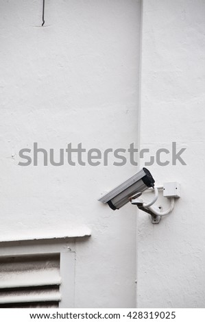 Surveillance video camera on white wall - stock photo