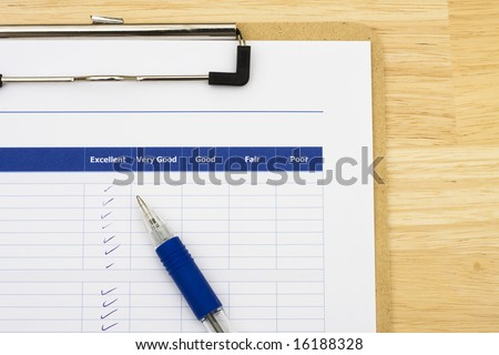 Survey attached to clipboard sitting on table with blue pen, excellent customer service - stock photo