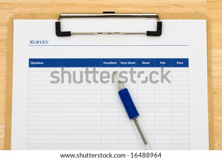 Survey attached to clipboard sitting on table with blue pen, excellent customer service