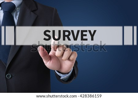 SURVEY Businessman hands touching on virtual screen and blurred city background - stock photo