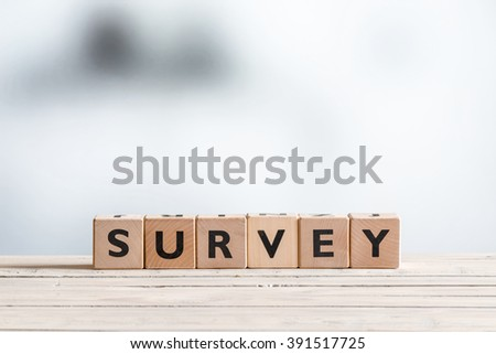 Survey sign made of blocks on a wooden table - stock photo