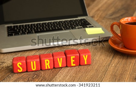Survey written on a wooden cube in a office desk - stock photo