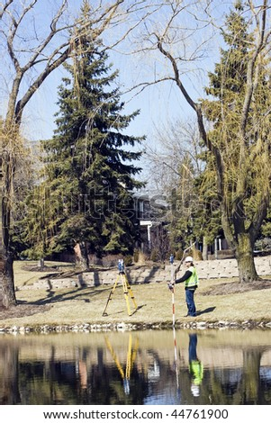 Surveying by the lake in residential area. - stock photo