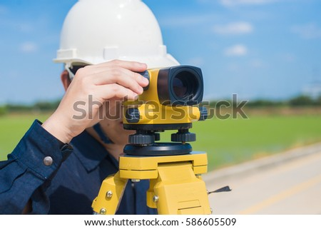 Surveying engineer is reading values of level for prepare the construction site by surveying equipment to check the leveling.