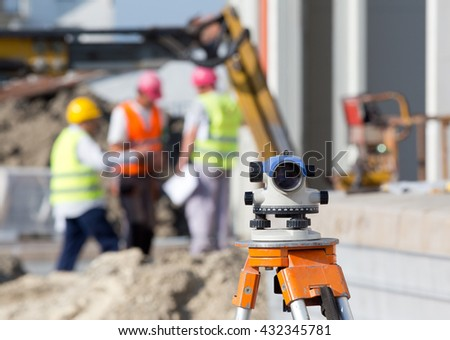 Surveying measuring equipment level theodolite on tripod at construction site with workers in background - stock photo