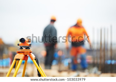 Surveying measuring equipment level transit on tripod at construction building area site - stock photo