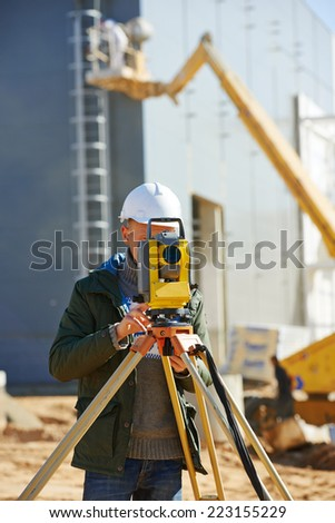 Surveyor builder worker with theodolite transit equipment at construction site outdoors during surveying work - stock photo