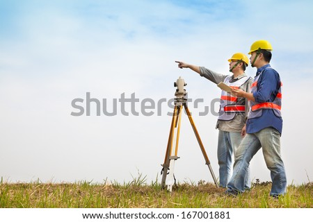 Surveyor engineer making measure with partner on the field - stock photo