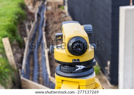 Surveyor equipment optical level at construction site - stock photo