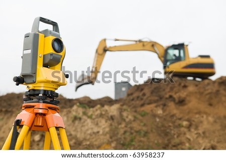 Surveyor equipment theodolite on tripod at building area in front of working construction machinery loader - stock photo