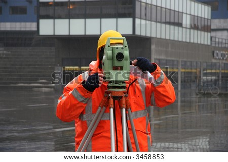Surveyor measuring land for construction with theodolite - stock photo