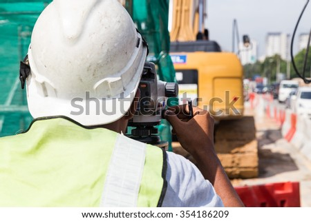 Surveyor operating the dumpy automatic level instrument at construction site