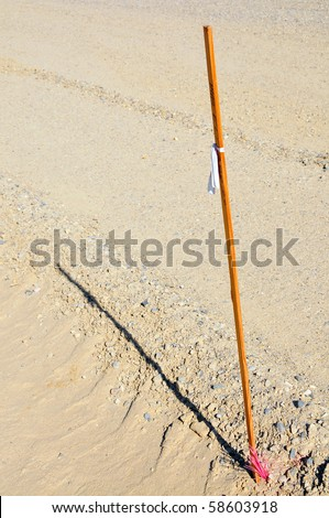 Surveyor's stake used to mark lines and grades on a road building project - stock photo
