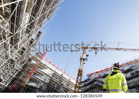 surveyor with instrument, surveying large building-site, super-.wide perspective - stock photo
