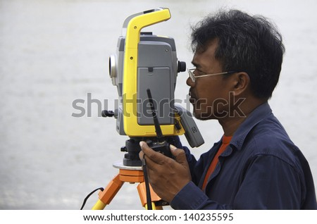 Surveyor worker make data collection with total station surveying, theodolite at construction site. - stock photo