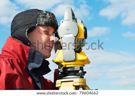 Surveyor worker make data collection with total station theodolite at construction site - stock photo
