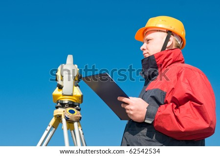 Surveyor worker making measurement in a field with theodolite total station equipment