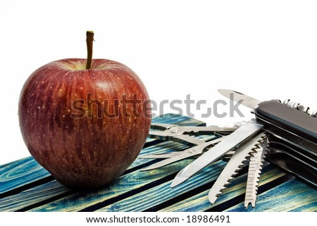 Survival: a red apple with a Swiss knife on a wooden board against a white background. - stock photo