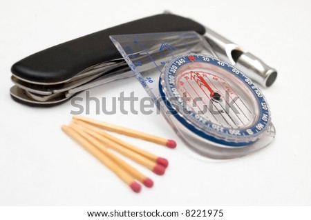 Survival items: Matches, compass, knife, and whistle - stock photo