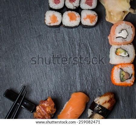 sushi and rolls on black background top view - stock photo