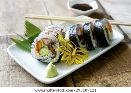 Sushi and wasabi in a white plate on a wooden table. - stock photo