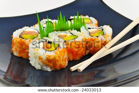 Sushi California Philly rolls appetizer with rice, avocado, and salmon on square blue plate w/ chopsticks - stock photo