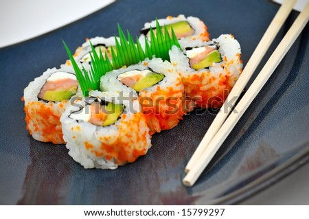 Sushi California rolls with rice, avocado, and salmon on a blue plate with chopsticks. - stock photo
