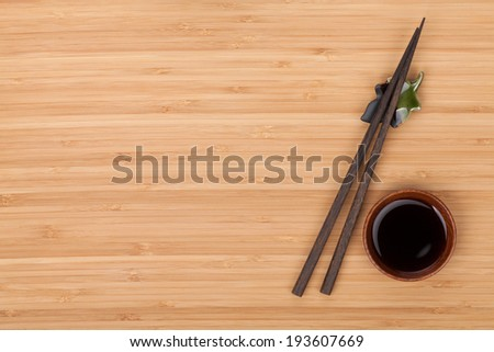 Sushi chopsticks and soy sauce bowl over bamboo table with copy space - stock photo