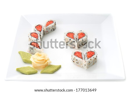 Sushi forming hearts and flower shapes on white square dish - stock photo