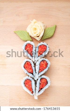 Sushi forming hearts and flower shapes on wooden cutting board - stock photo