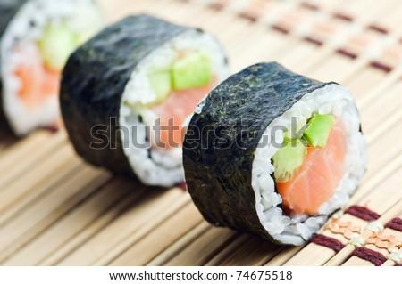 sushi in row on bamboo mat - stock photo