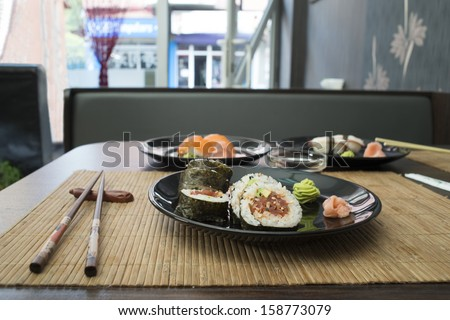 Sushi in sushi bar. Table and ration sushi - stock photo