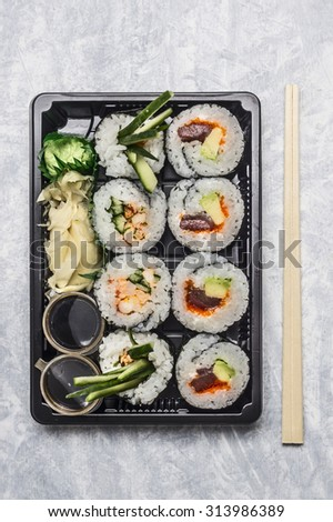 sushi menu in black transport box or bento box on gray background, top view, close up - stock photo
