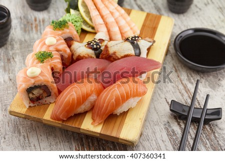Sushi nigiri set on a gete plate with wasabi soy sauce and chopsticks over wooden background - stock photo