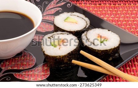 Sushi on a black plate on a red mat with chopsticks - stock photo