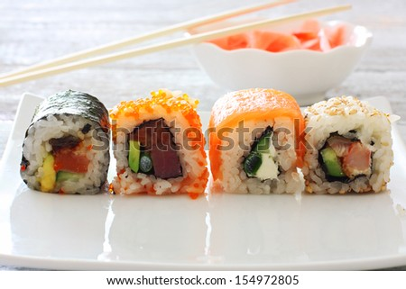 Sushi pieces collection on white plate over wood table - stock photo