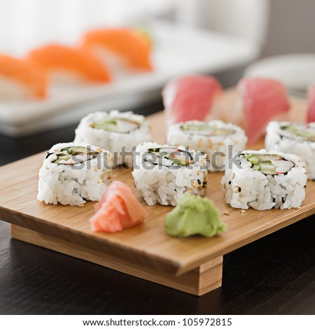 sushi - platter with california roll and nigiri in background - stock photo