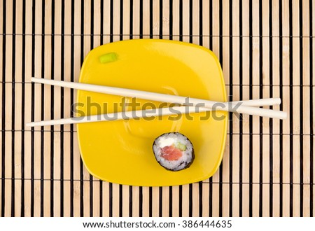 Sushi roll and chopsticks in yellow saucer over bamboo mat - stock photo