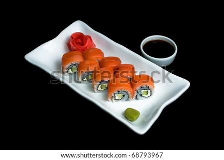 """Sushi Roll """"Philadelphia"""" with sauce on the plate on a black background - stock photo"""