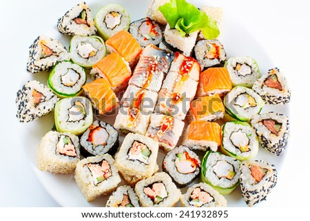 Sushi roll set on a white dish. Different japanese food. Sesame, shrimp, salmon, eel. Selective focus, top view. - stock photo