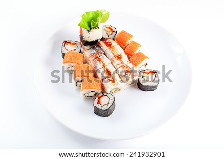Sushi roll set on a white dish. Different japanese food. Shrimp, sesame, salmon, eel. Selective focus, top view. - stock photo