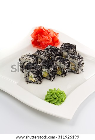 Sushi roll with black caviar with ginger and wasabi on a white plate - stock photo