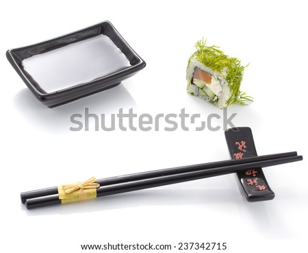 Sushi roll with black ceramic plate with soy sauce and black chopsticks isolated - stock photo