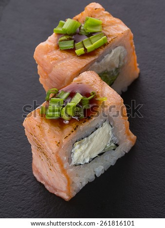 Sushi roll with onion on a stone pate - stock photo