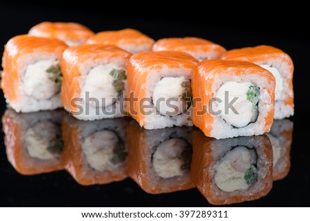 Sushi Roll with Salmon and shrimp over  black background with reflection