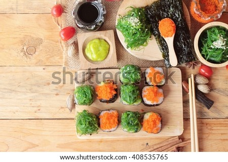 Sushi roll with seaweed salad and shrimp eggs - stock photo