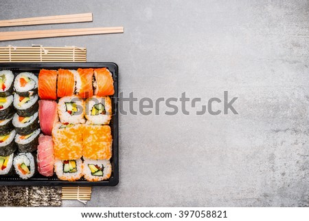 Sushi rolls and chopsticks on gray stone background, top view, place for text. - stock photo